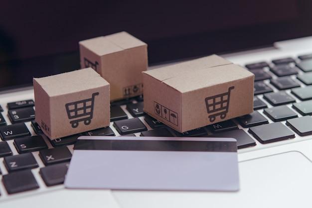 Покупки онлайн - бумажные коробки или посылки с логотипом корзины покупок и кредитной картой на клавиатуре ноутбука. служба покупок в интернете и предлагает доставку на дом.