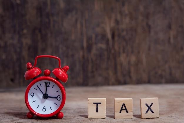 木製のアルファベットのブロックと赤い目覚まし時計、テーブル暗い板木製テーブルの上の税金
