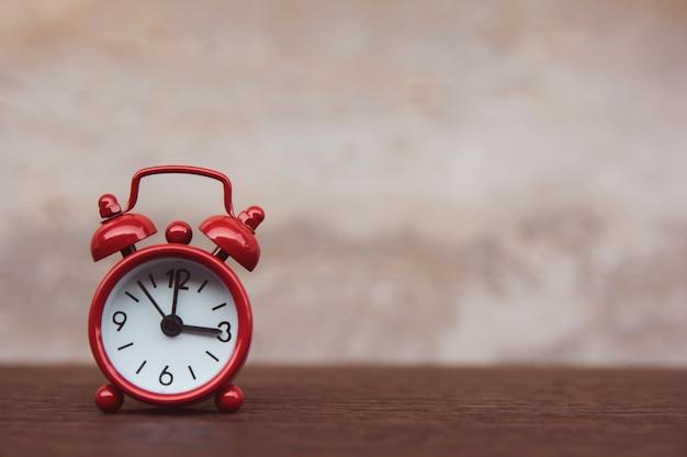 コピースペースを持つ木製のテーブル暗い板に赤い目覚まし時計
