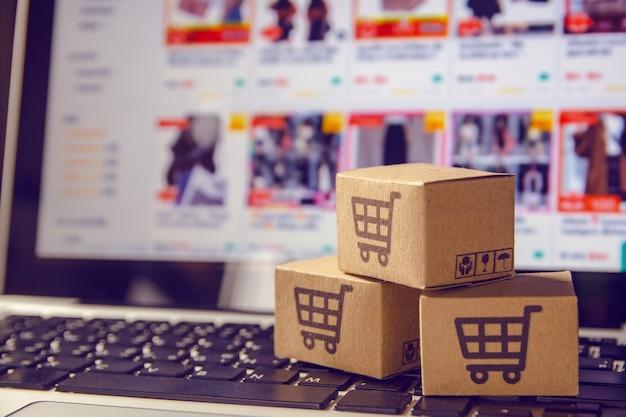 ノートパソコンのキーボードのトロリーにショッピングカートのロゴが入った小包または紙のカートン