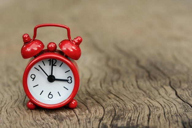 木製のテーブルに赤い目覚まし時計