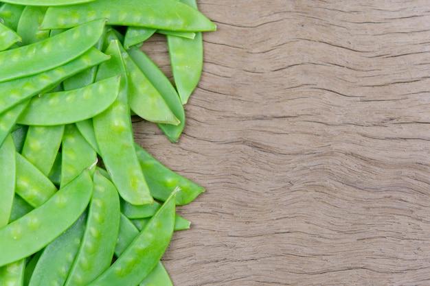 Зеленые стручки гороха на деревянный стол