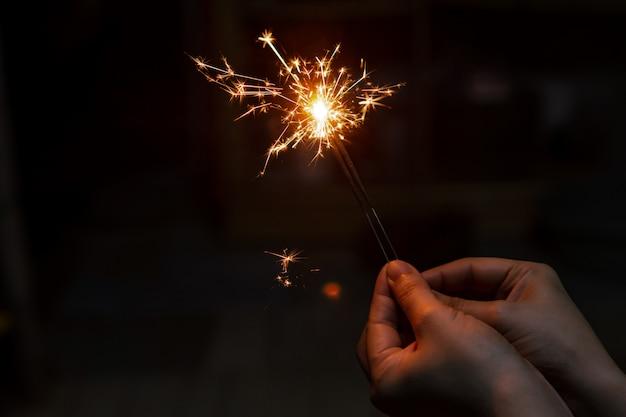 燃える線香花火を持っている女性の手