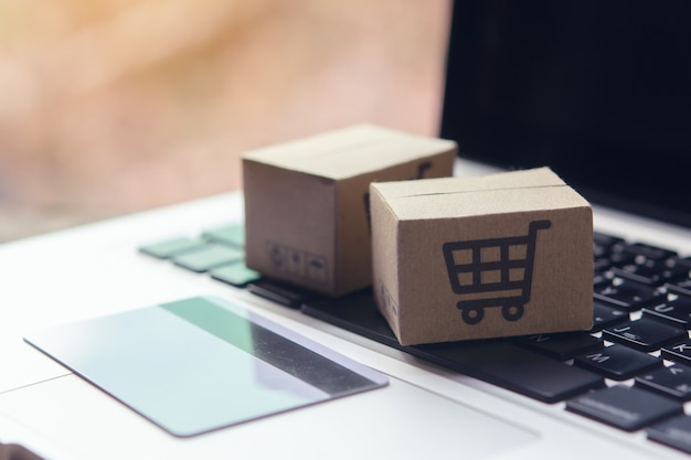 Бумажные коробки с логотипом корзины покупок и кредитной карты на клавиатуре ноутбука.