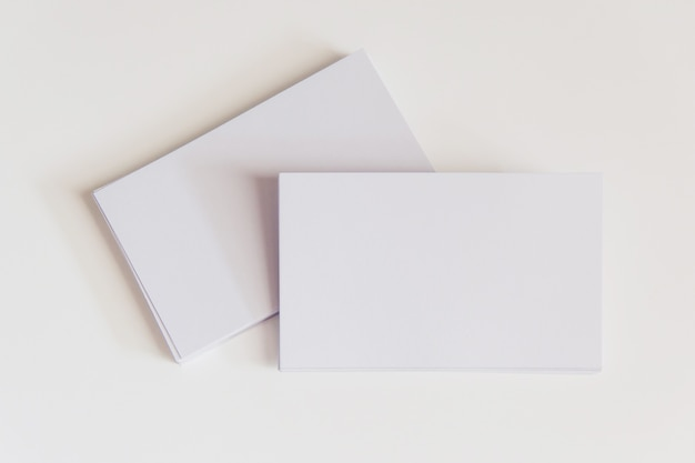 空白の白い名刺のスタック。クリッピングパスと白い背景のモックアップ名刺