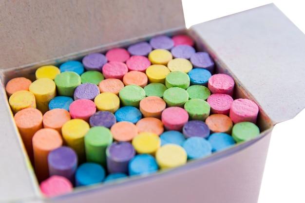Красочный мел в картонной коробке, коробка мела на белом фоне