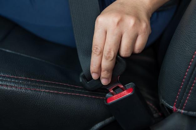 カーシートベルト。女性は車のシートベルトを固定します安全な運転。手持ちの安全ベルト。