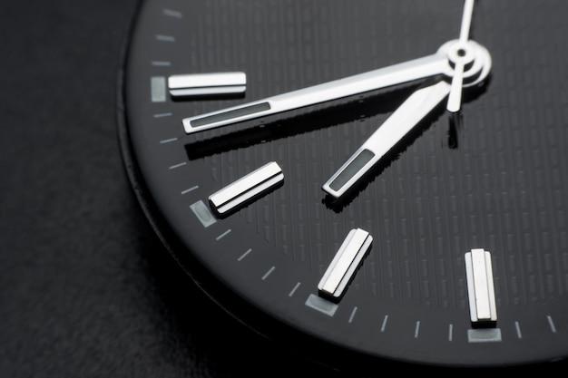 黒い時計の顔の背景に時計回りに閉じる。レトロスタイルの腕時計