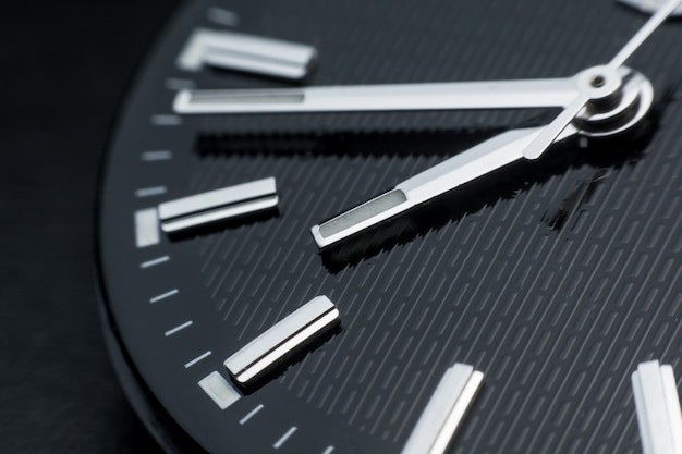 Закройте вверх по часовой стрелке на фоне черных часов. наручные часы в стиле ретро
