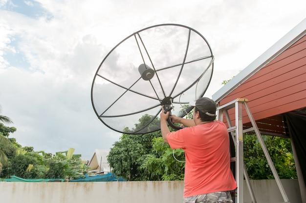 男の技術者が屋根の上に衛星放送をインストールしています。サテライトインストーラ