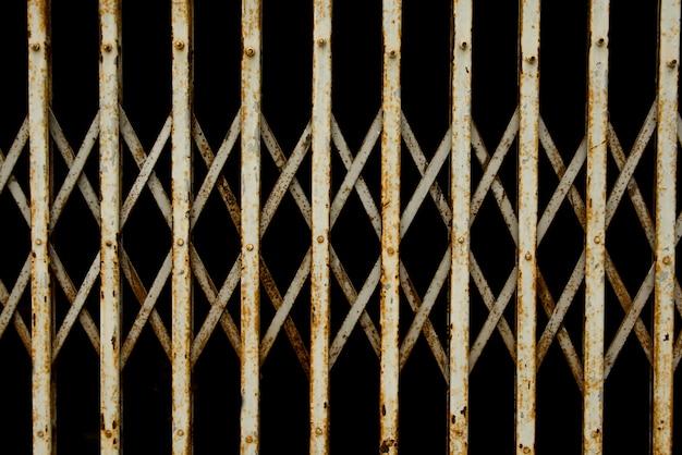 古い折り畳み式の金属門。古い錆びた鉄スライドドア