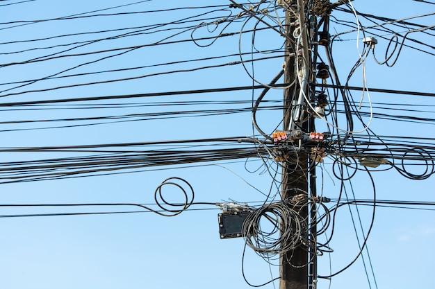 青い空に対して都市の極に多くのケーブルと電線を集めます。