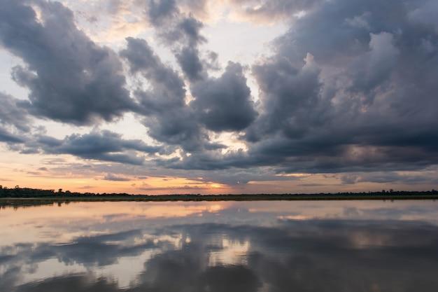 湖の夕日。上の雷雨の前の嵐の雲の後ろの美しい夕日