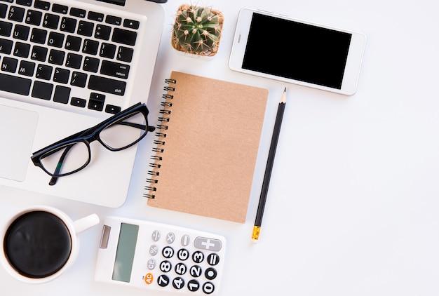 ホワイトオフィスデスクテーブル、ワークスペースオフィスのラップトップ、スマートフォン、ペン、電卓、眼鏡