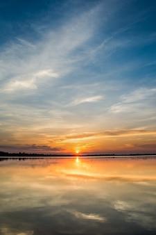 湖の夕日。湖の風景以上の背景の上の雲の後ろに美しい夕日。