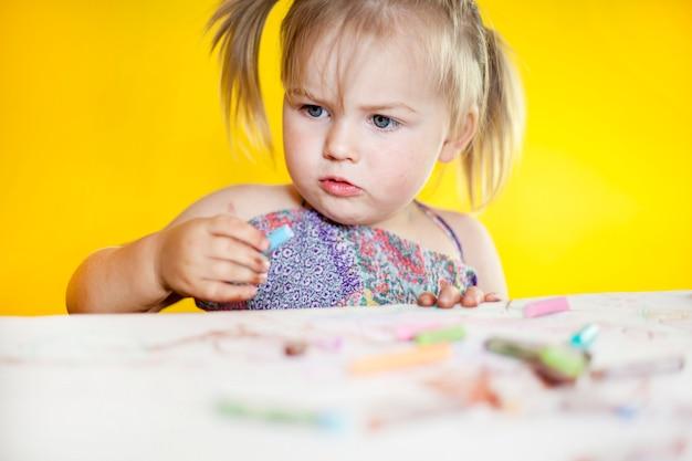 美しい少女はクレヨンを描画します