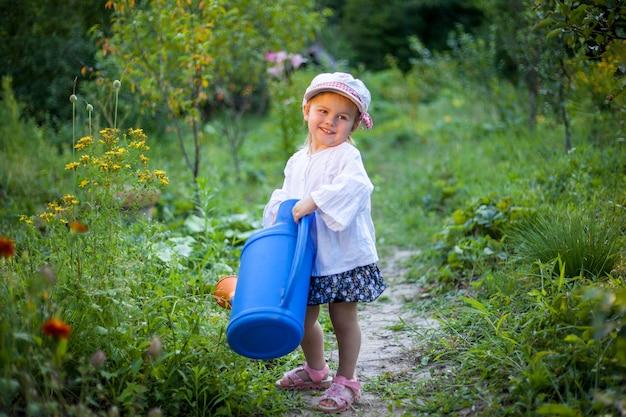 Красивая белая девушка поливает цветы из лейки