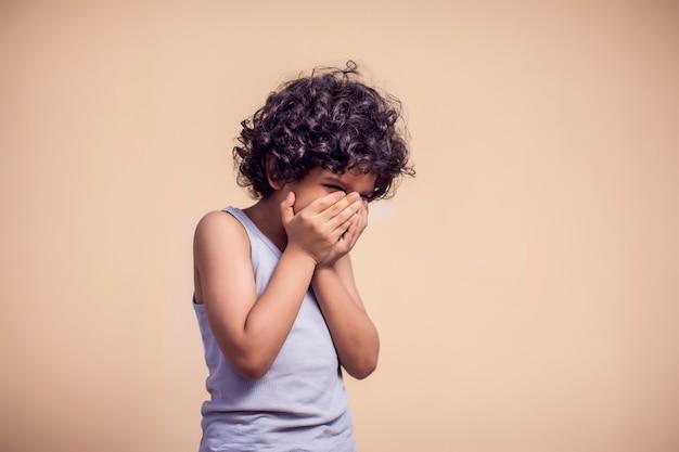 巻き毛を持つ悲しい子供男の子の肖像画。子供と感情の概念