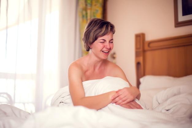 若い悲しい女性は彼女のベッドで横になっていると泣いています。人とライフスタイルのコンセプト