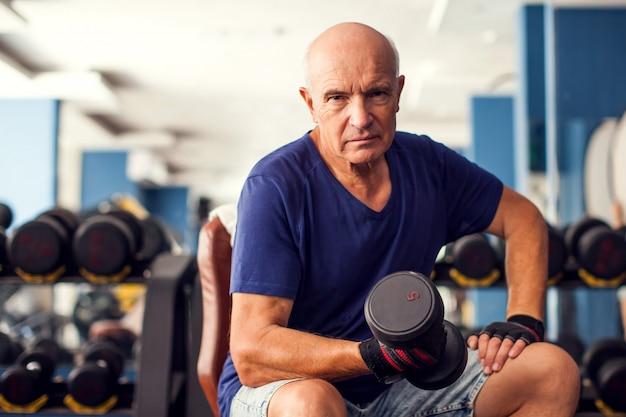 ダンベルでジムのトレーニングで年配の男性の肖像画。人、健康、ライフスタイルのコンセプト