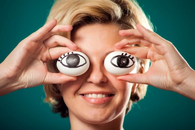 Портрет счастливой женщины с короткими светлыми волосами держит яйца, как глаза. люди, образ жизни и концепция питания