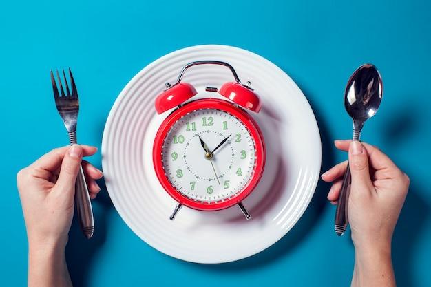 色の背景にスプーンとフォークで白いプレートに赤い目覚まし時計。食べ物と食事のコンセプト