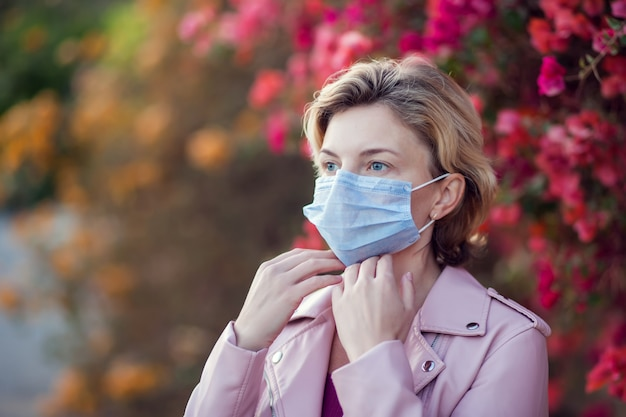 屋外の医療フェイスマスクと短いブロンドの髪を持つ女性の肖像画。人、医療、医学の概念。