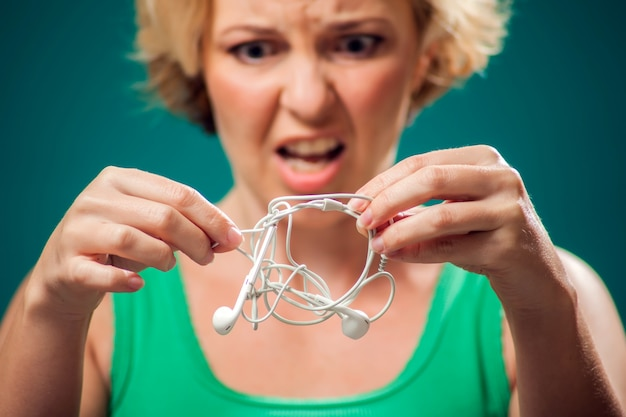 Сердитая женщина, держащая белый запутанный наушник, пытающийся распутать это. люди и технологии концепция