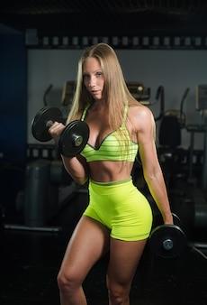 美しいセクシーな運動筋肉の若い女の子。ジムでフィットネス女の子電車