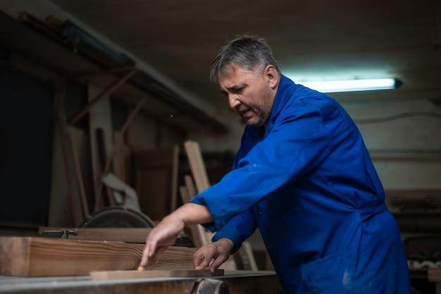 Плотник за работой в своей мастерской, обработка древесины на деревообрабатывающем станке