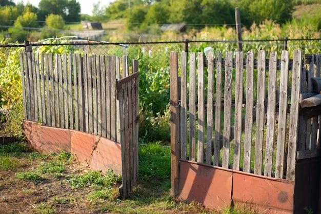 村の農場の古いフェンス。オープンゲート