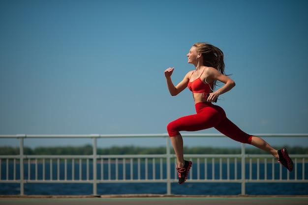 海岸を走っている若いフィットネス女性。健康的なライフスタイルのコンセプト