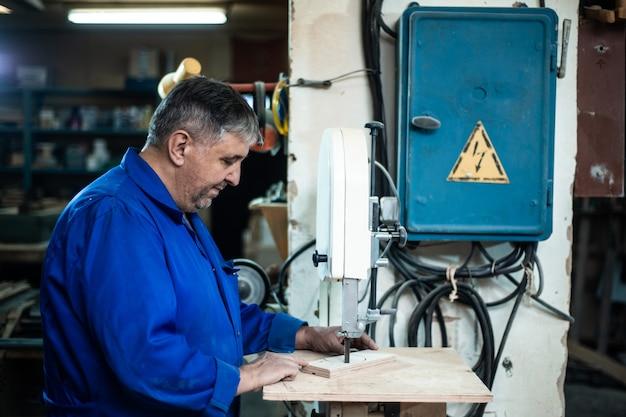 従業員は掘削プレスの助けを借りてワークショップでアイテムを掘削します