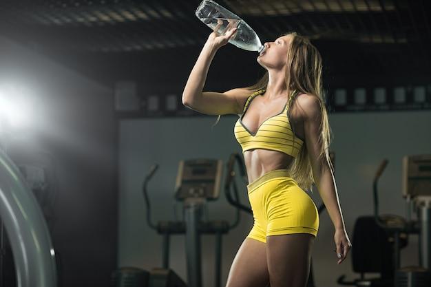 トレーニングの後にさわやかに。美しい女性のジムで水を飲む