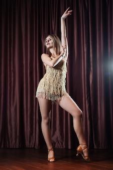 Красивая девушка в золотом платье танцует на сцене против красных штор
