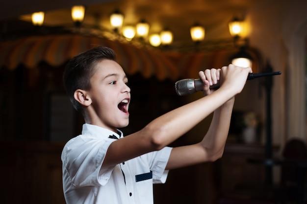 レストランでマイクに向かって歌っている白いシャツの少年。