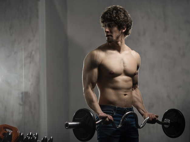 筋肉男は、ジムでバーベルで上腕二頭筋をトレーニング、手のトレーニング