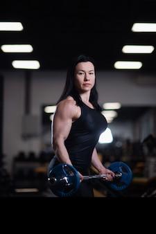 フィットネス女の子は、ジムでバーベルで上腕二頭筋を訓練します。