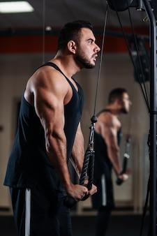 Мускулистый мужчина во время тренировки в тренажерном зале тренирует трицепс