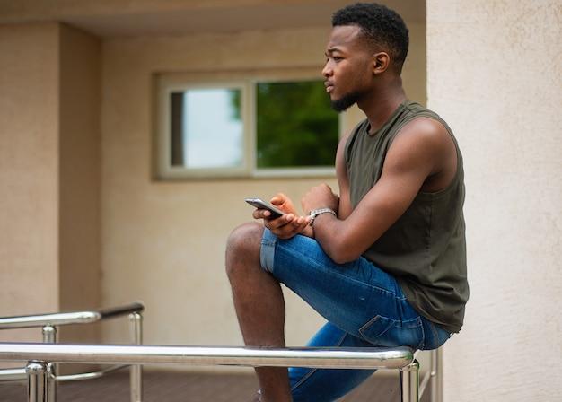 流行に敏感な、スマートフォンを使用している若い男。