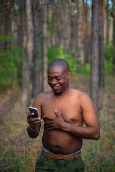 スマートフォンを押しながら笑ってシャツなし男
