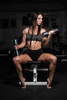 女性はジムで列車します。アスレチック女は彼女の二頭筋をポンピング、ダンベルトレーニング