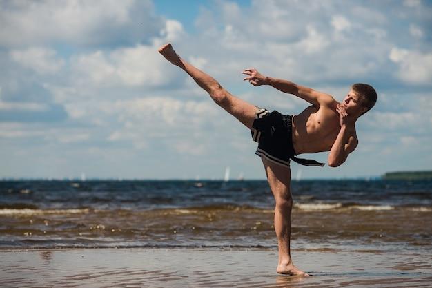 キックボクサーは夏に海に対して野外で蹴ります。