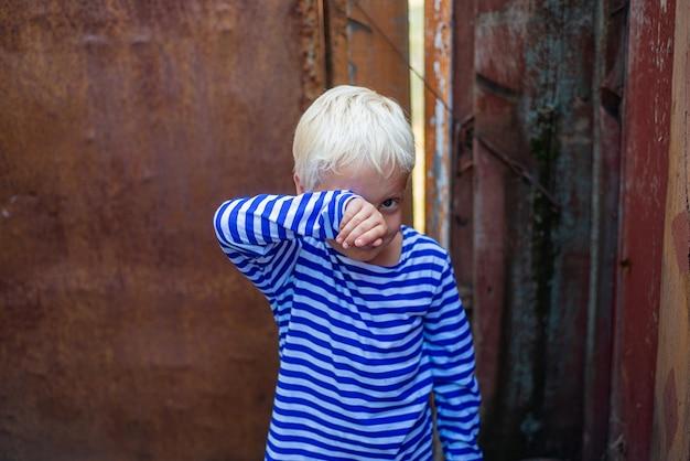 さびたドアの背景に小さな男の子は彼の手で涙を拭きます。