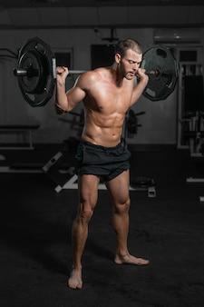 足をポンピング、バーベルを持つ男性のトレーニング