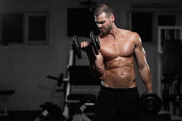 男はジムでトレーニングします。アスレチック男はダンベルでトレーニングし、上腕二頭筋をポンピングします。