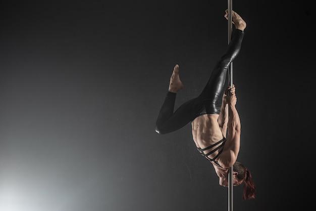 パイロンを持つ男男性ポールダンサーの踊り