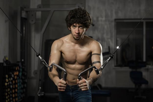 ハンサムな運動男はジムで彼の胸を訓練します。男性のフィットネス