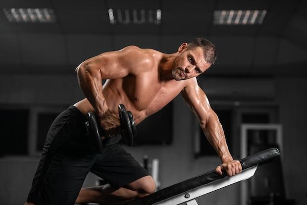 男はジムでトレーニングします。アスレチック男はダンベルでトレーニングし、彼の上腕二頭筋をポンピングします。
