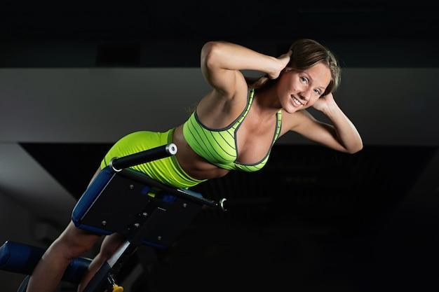 スポーツ若い女性のジムでトレーナーバックマシンでのエクササイズ